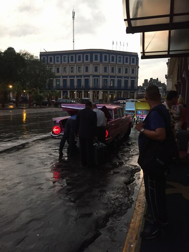 A classic taxi picks up from outside the hotel during the rain